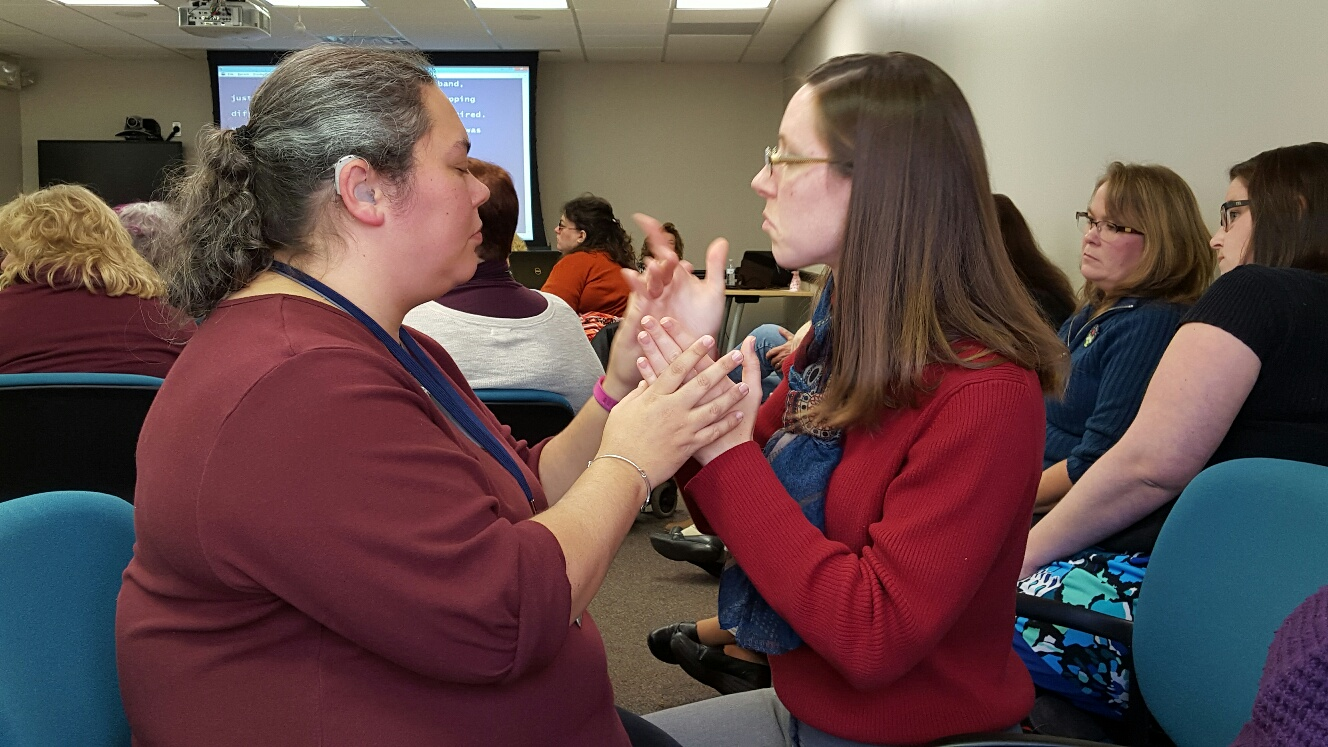 Photo of two women at meeting using Sign Language